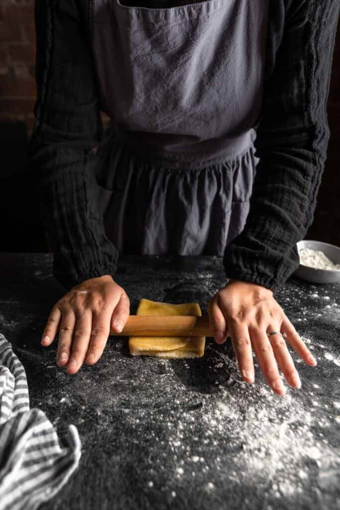 rolling the folded pasta dough with a small rolling pin