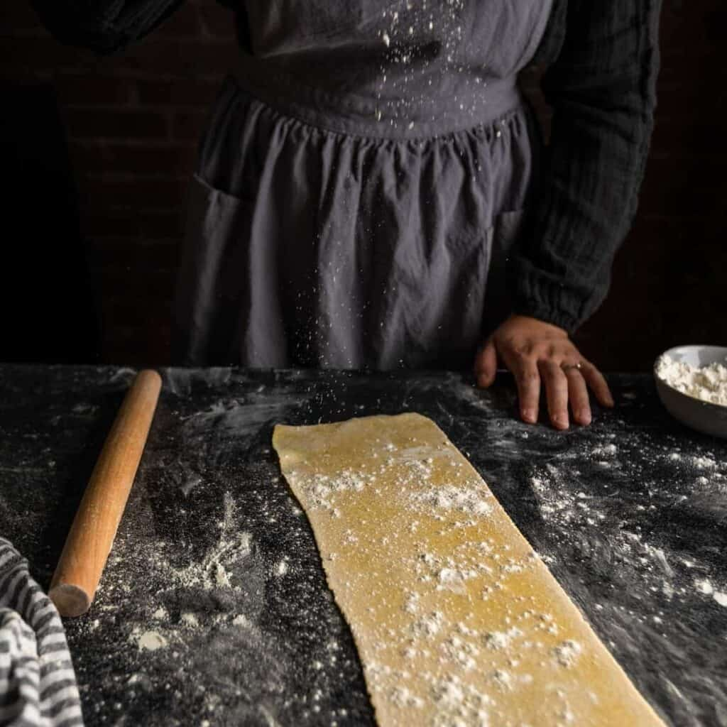 dusting a sprinkle of flour over a sheet of pasta dough