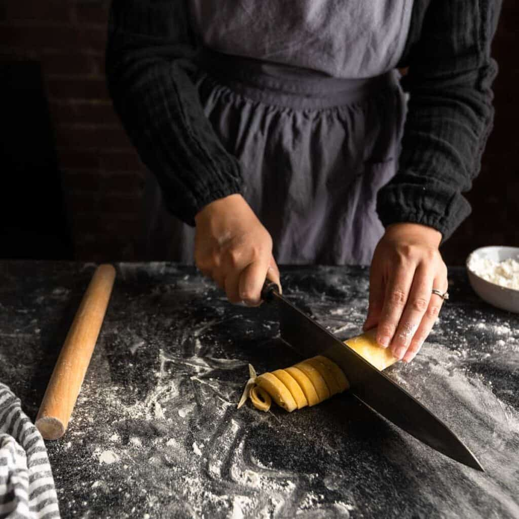 a woman using a sharp knife to cut a log of rolled pasta dough into spirals of homemade fettuccine pasta