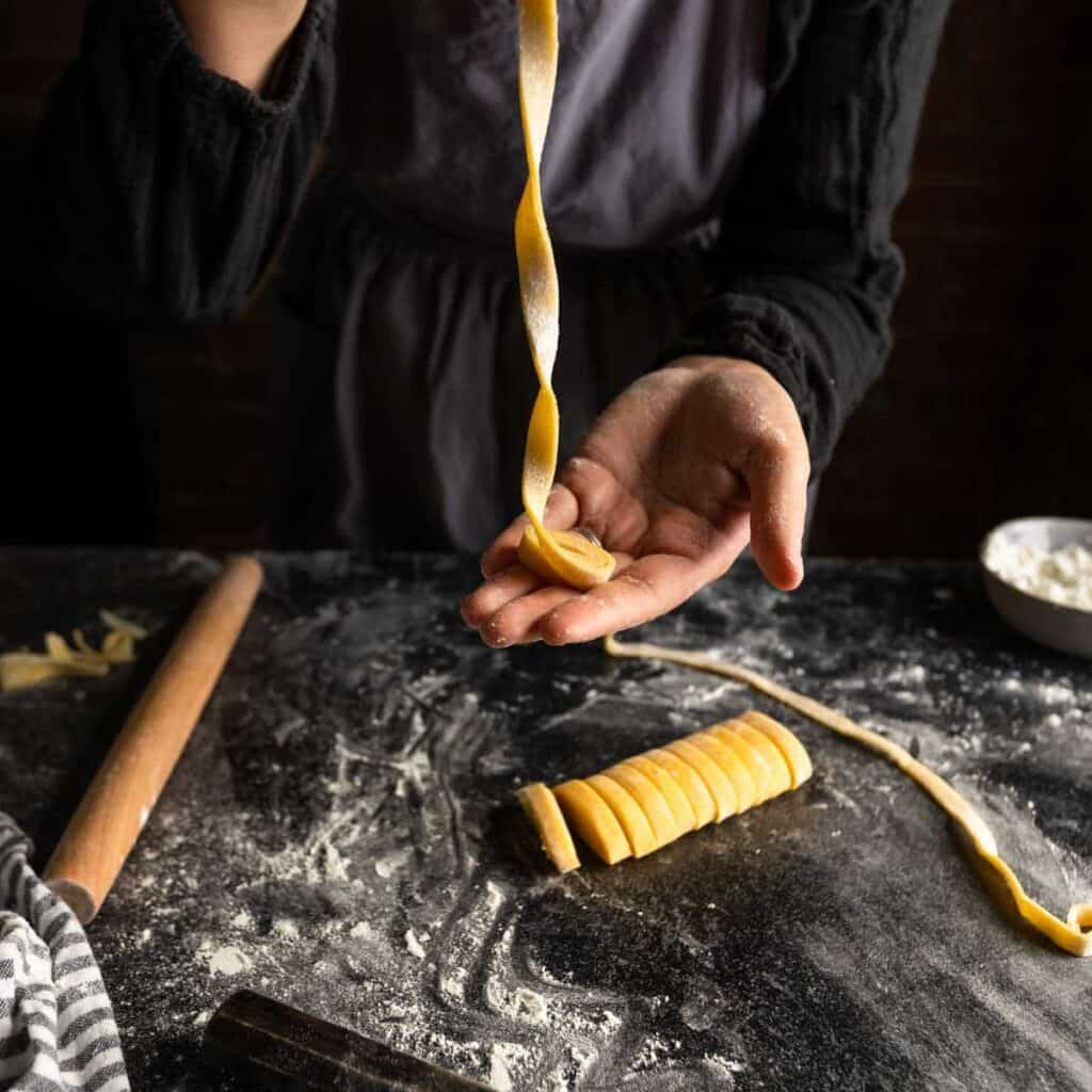 a woman unraveling a little ribbon of fettuccine pasta
