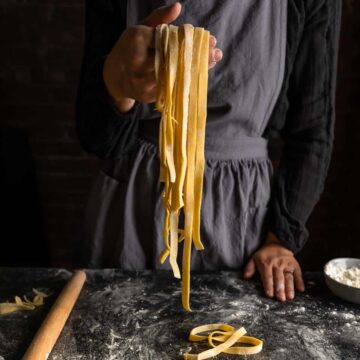 An aproned woman holding up a handful of homemade fettuccine pasta noodles