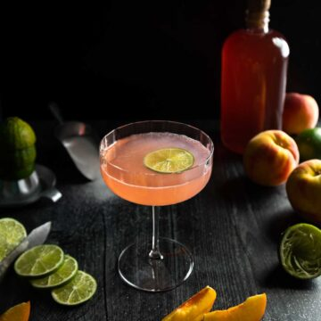 A pink peach daiquiri in a fluted coupe glass with a lime wedge garnish surrounded by slices of peaches, limes and a bottle of peach syrup