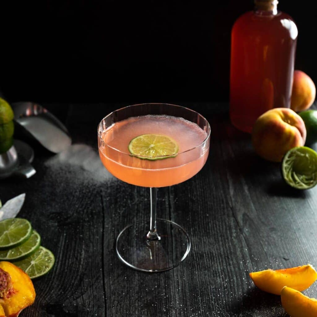 A peach daiquiri in a fluted coupe glass with a lime wheel garnish