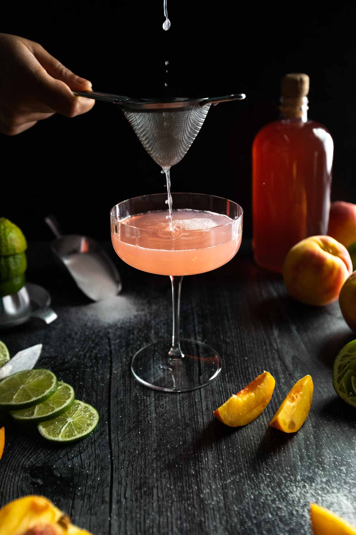 The last drops of a peach daiquiri being poured and strained through a tea strainer into a coupe glass surrounded by sliced limes and peaches