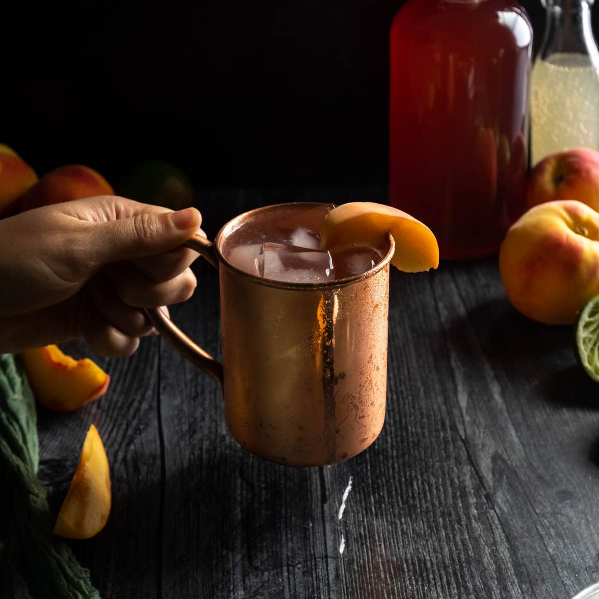 A hand picking up an icy copper mug of Peach Moscow Mule garnished with a fresh peach slice