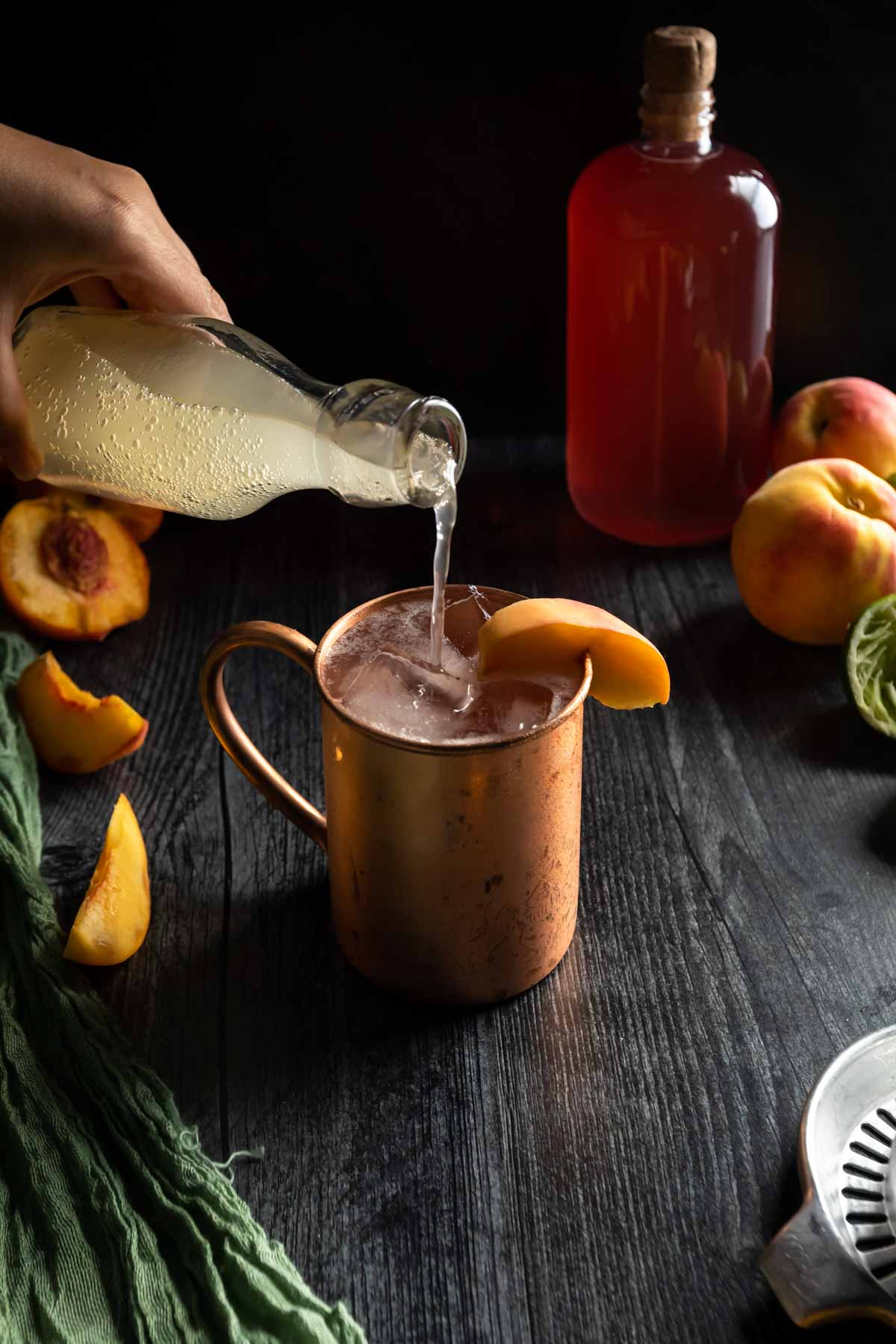 Topping a copper mug Peach Moscow Mule with a pour of ginger beer