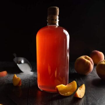 A corked glass bottle of peach syrup surrounded by whole and sliced peaches and a scoop or sugar