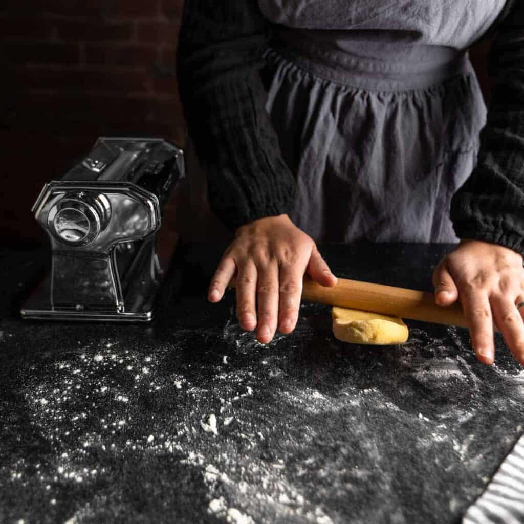 A woman rolling a piece of pasta dough with a small rolling pin on a floured surface