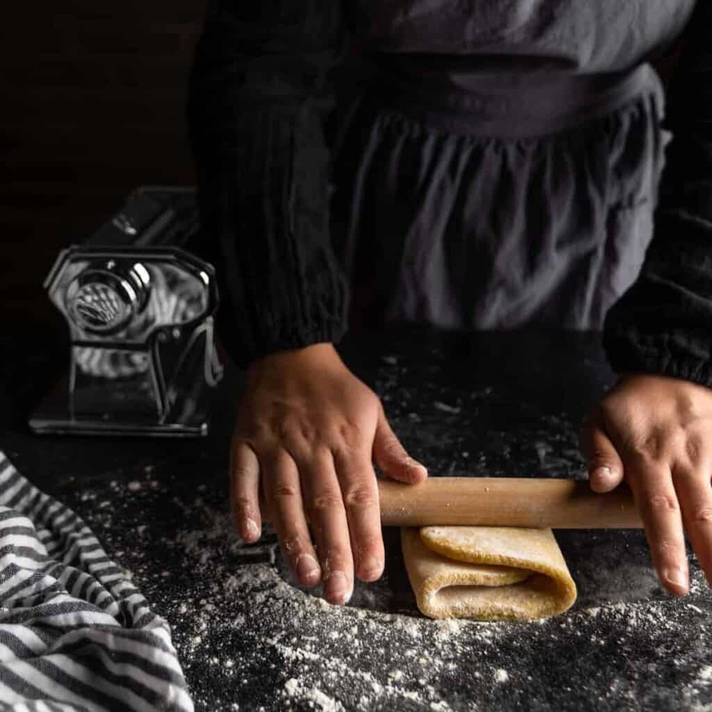 A woman rolling a piece of trim-folded pasta dough on a floured surface