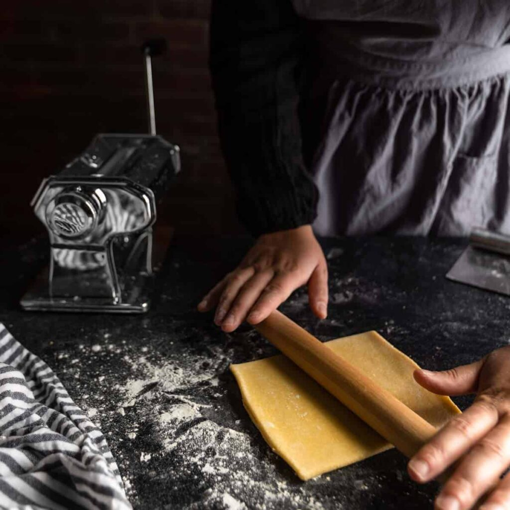 A small square of semolina pasta dough being rolled with a small rolling pin
