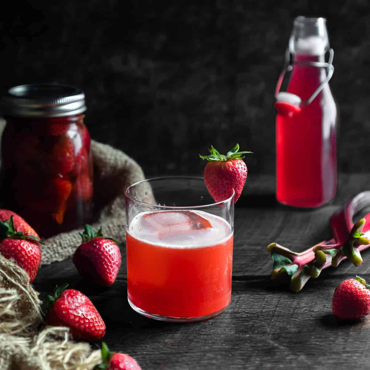 A strawberry rhubarb whiskey sour with a strawberry garnish. A jar of strawberry infused whiskey, fresh strawberries, stalks of rhubarb and a bottle of rhubarb syrup are in the background.