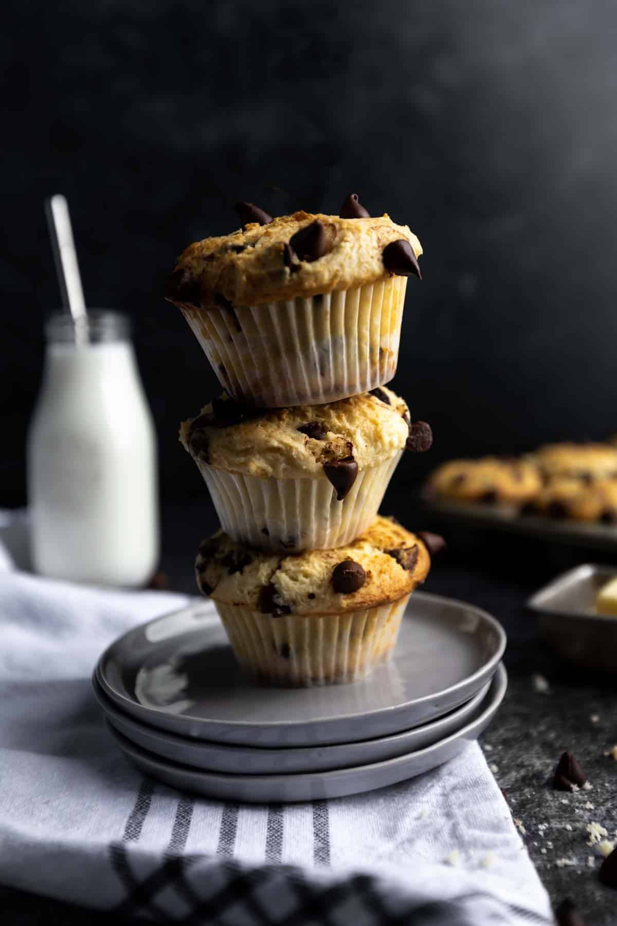 three chocolate chip muffins stacked on top of each other.
