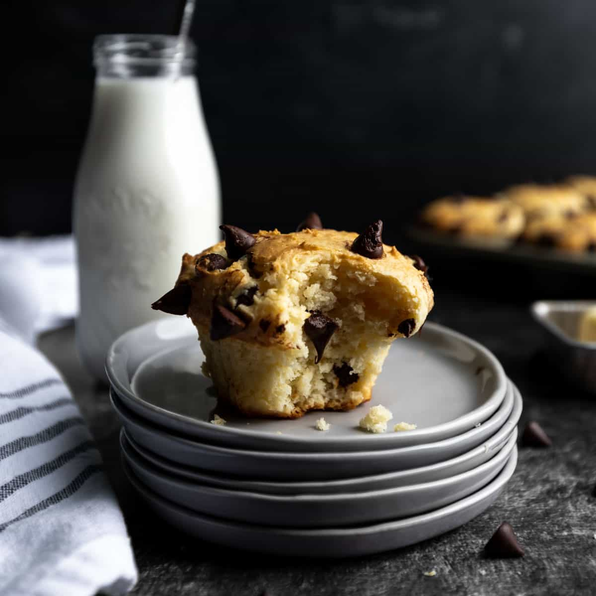 A chocolate chip muffin on a stack of plates, next to a jar of milk.