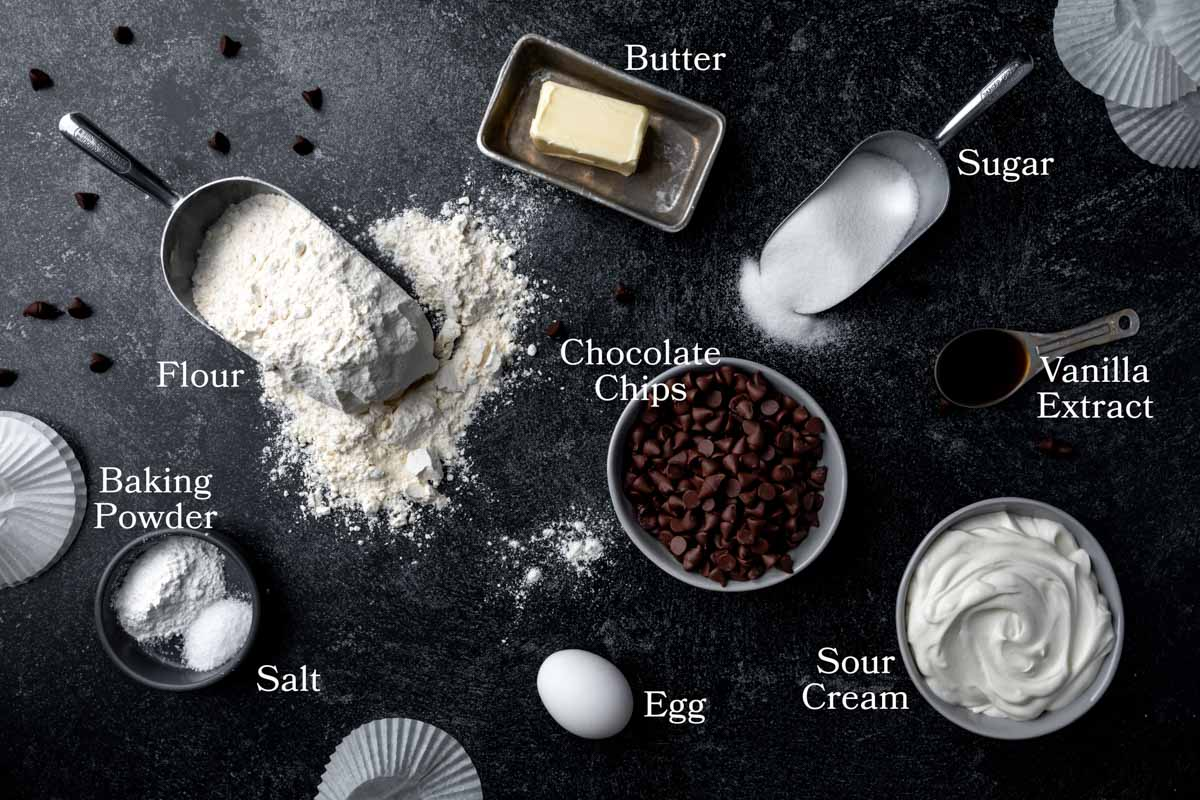 ingredients shot for the chocolate chip muffins: flour, butter, sugar, vanilla extract, sour cream, egg, chocolate chips, baking powder and salt