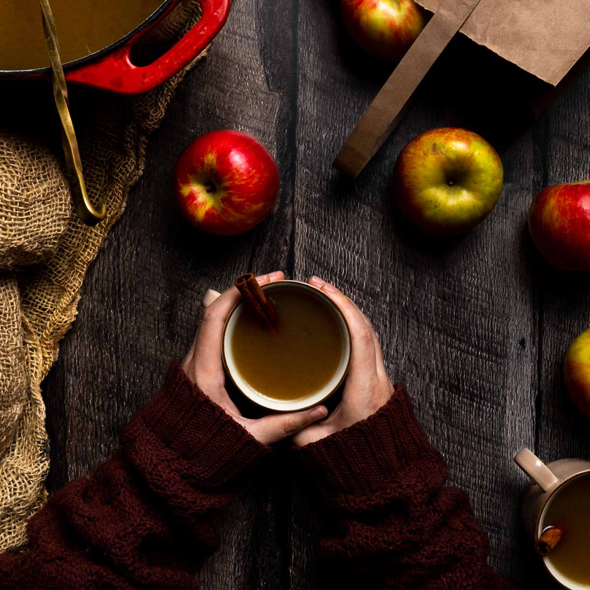 Two hands cradling a mug of homemade spiced cider next to apples and burlap