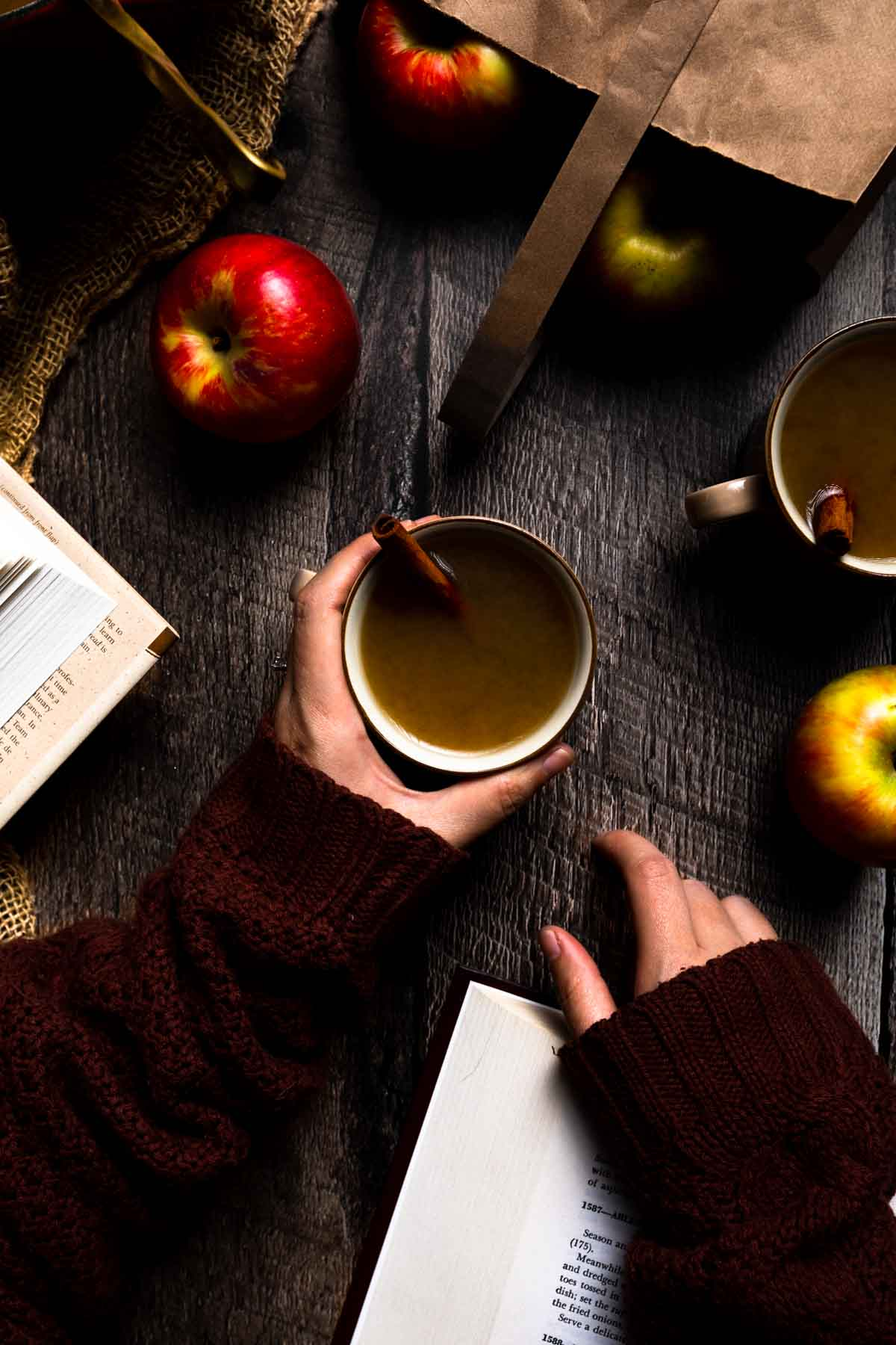 A hand holding a mug of hot apple cider near open books and a bag of apples