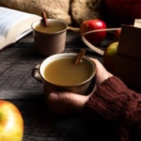 A hand holding a mug of hot apple cider next to apples, books, and another mug