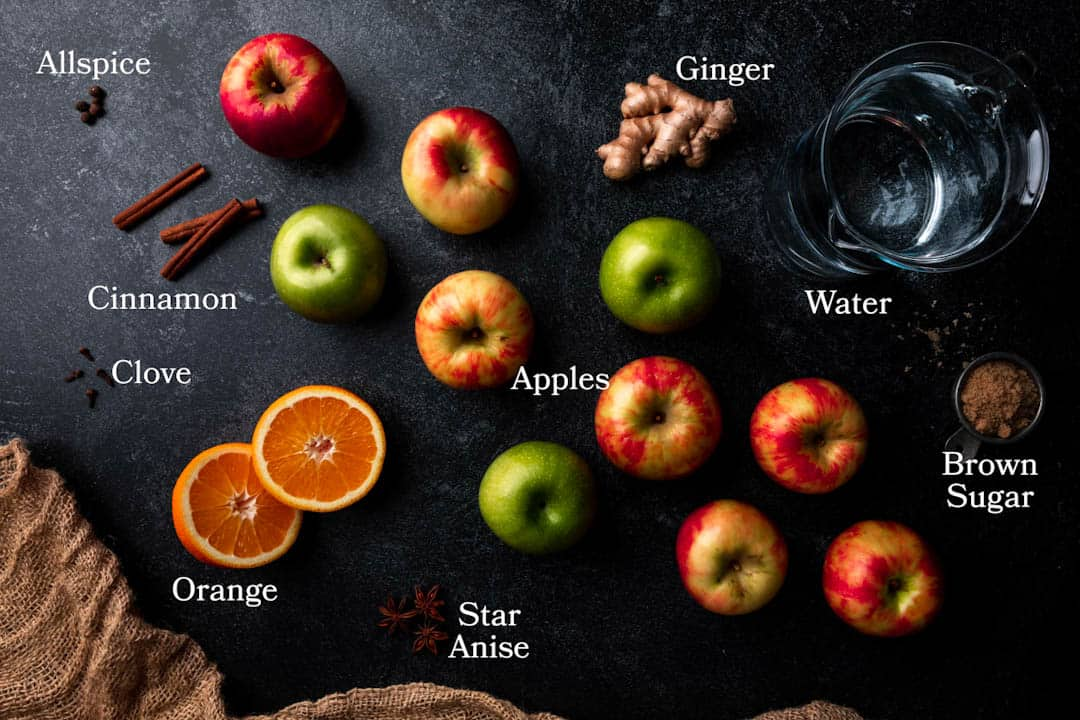 Picture of ingredients for homemade apple cider including apples, orange, ginger, brown sugar, star anise, clove, cinnamon, allspice and water.